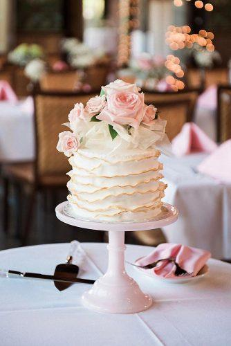 small wedding cakes on a pink stand with ruffles of cream and pink roses allie siarto via instagram