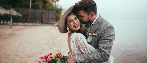 things brides regret not doing at their wedding bride and groom happy at the beach featured