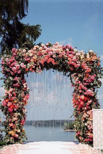 wedding arch decoration ideas a stunning wedding arch densely decorated with roses and garlands on the background of a pond flowerbazar via instagram