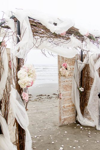 old door wedding decoration on the beach white doors with flowers decorations with wooden branches and cloth c baron photography via instagram
