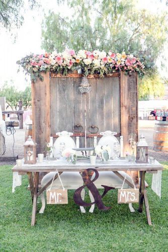old door wedding decoration wedding table of the bride and groom on the background of the door decorated with a chandelier and flowers leah marie photography