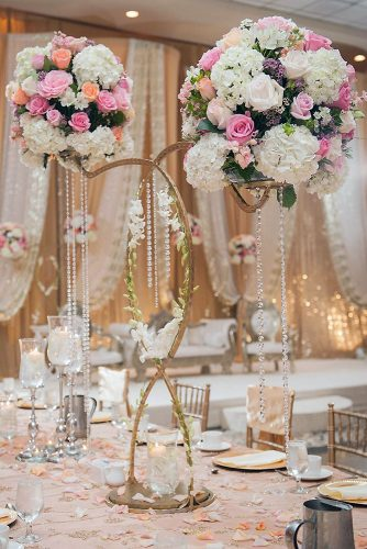 tall wedding centerpieces a golden stand of unusual shape decorated with beads and greens with balls of white and pink flowers luxury wedding photo via instagram