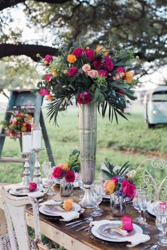 tall wedding centerpieces in a high metallic silvery vase bright burgundy and yellow roses with greens at a reception in boho style elisheva golani via instagram