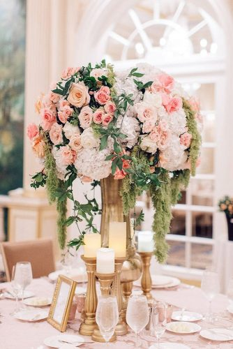 tall wedding centerpieces in a tall golden vase surrounded by candles a bouquet of coral roses and greens cascade kenzie victory via instagram