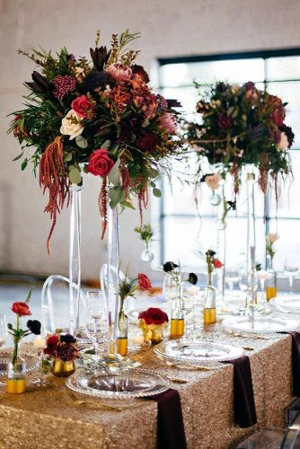 tall wedding centerpieces on a golden tablecloth on a transparent stand greens red and white roses tiffani jones via instagram