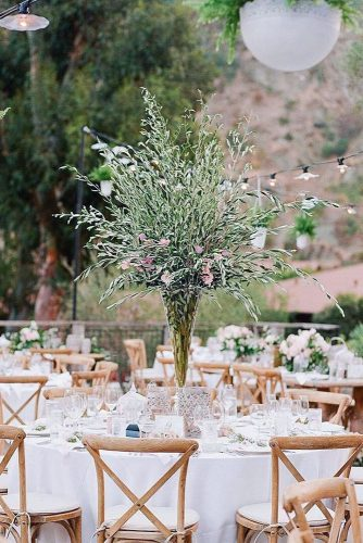 tall wedding centerpieces on a table with a white tablecloth in a vase greens and rare pink flowers cory & gloria mccune via instagram