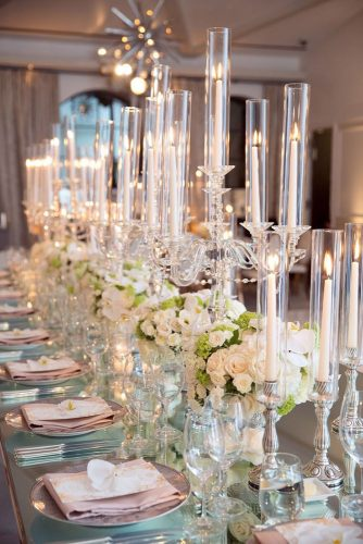 tall wedding centerpieces on the table candlesticks with white candles and white roses with bright greens melody melikian photography via instagram