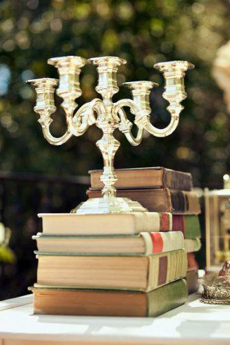 non floral wedding centerpieces a stack of books and a golden candlestick retrospect images