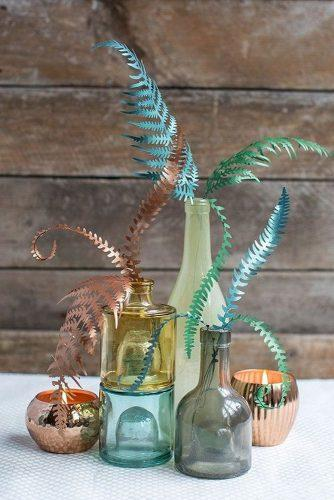 non floral wedding centerpieces in the glass bottles of paper feathers tutorial from lia griffith