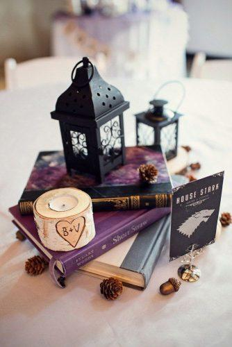 non floral wedding centerpieces on a pile of books a lantern and a candle melissa tuck photography