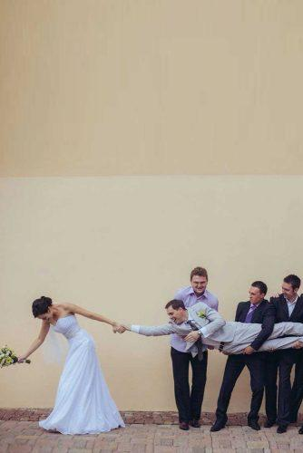 hilarious clever wedding photos bride pulls the groom from groomsmen creativa wedding photography