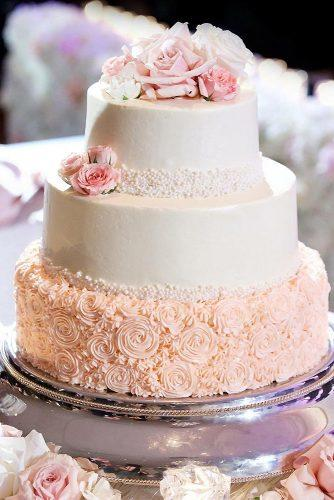 textured wedding cakes bottom layer pink with petals top layer white decorated with flowers inside weddings via instagram