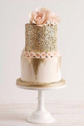 textured wedding cakes two tier covered with gold texture adorned with pink flowers lillian rose inc via instagram