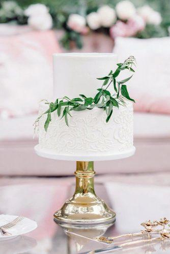 textured wedding cakes white small on a golden stand decorated with patterns and a twig of greenery monica jaramillo tatis via instagram