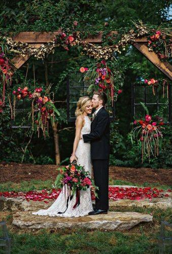 rustic wedding couple near rustic arch Amilia Photography