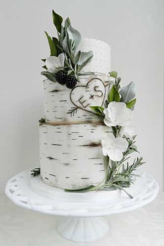 small rustic wedding cakes the birch bark with initials in the heart is decorated with white flowers with greens and berries the cake whisperer