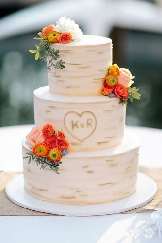 small rustic wedding cakes the birch bark with the initials in the heart is decorated with bright flowers troy grover