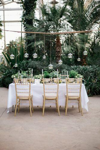greenery wedding decor green plants in pendant glass balls over the table amy fanton photography
