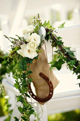 greenery wedding decor seat decorated with greenery with flower of wild rose with linen bag and horseshoe for good luck jess and nate studios