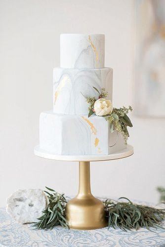 marble wedding cakes three tiered with golden elements and a delicate white flower with greens elegant wedding magazine via instagram