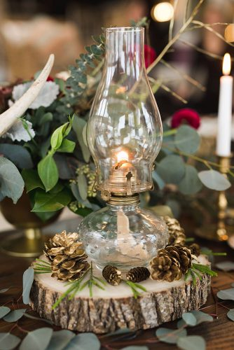 winter wedding decorations a lamp surrounded by pine cones on a wooden piece on the wedding table keira lemonis photography
