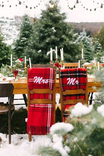 winter wedding decorations a wedding table on the street decorated with white candles of golden candlesticks and chairmasters with a red checkered scarf utah event wedding planner via instagram