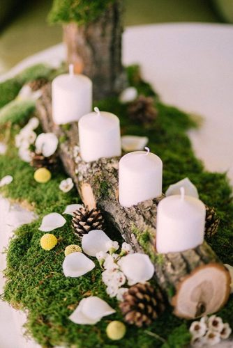 winter wedding decorations candlestick from a wooden branch with white candles surrounded by pine cones on a green moss muse books via instagram