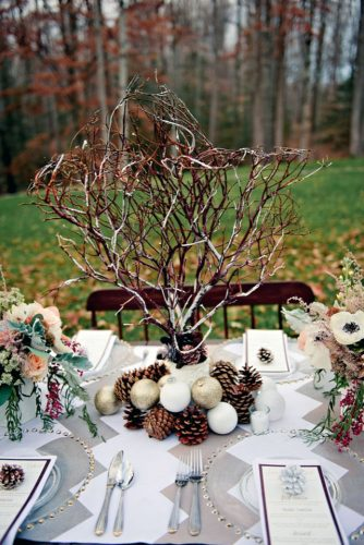 winter wedding decorations centerpiece with branches of fir cones and balls on the wedding table terri baskin photography
