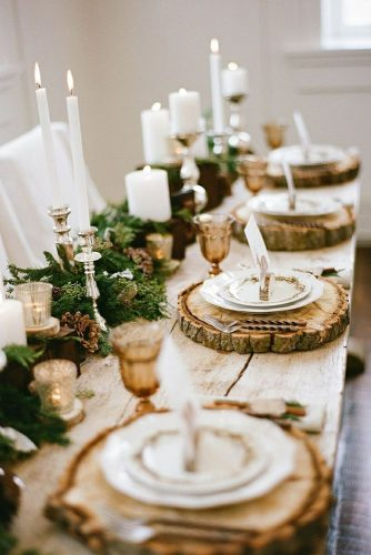 winter wedding decorations on a long wooden table decorated with fir tree branches with cones and candles plates on wooden slices jacque lynn photogaphy