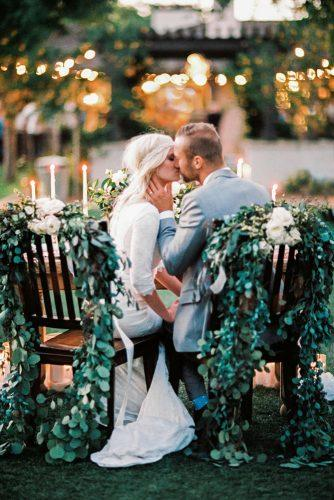 wedding photo shoot bride and groom at the wedding table are kissing at the table mary claire photography