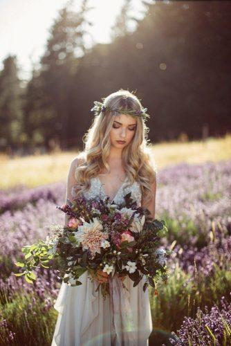 wedding photo shoot bride in flowers with bouquet in a field rivkah photography