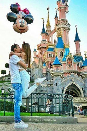 romantic marriage proposal in disneyland with tender kiss and baloons