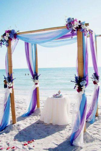 blue wedding theme arch at the beach blue and white tulle