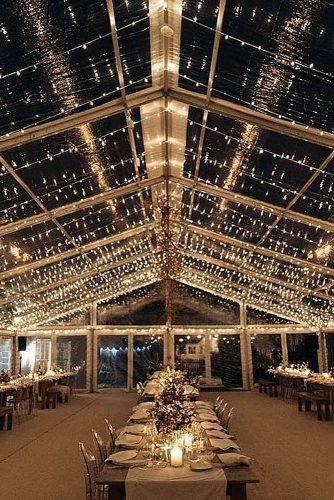 wedding tent transparent with light bulbs on the tables candles and flowers losberger us via instagram