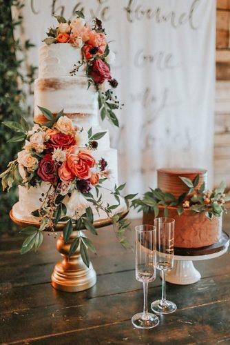beautiful wedding cakes tall white cake with fresh roses and greens small chocolate cake with greens nearby melissa marshall