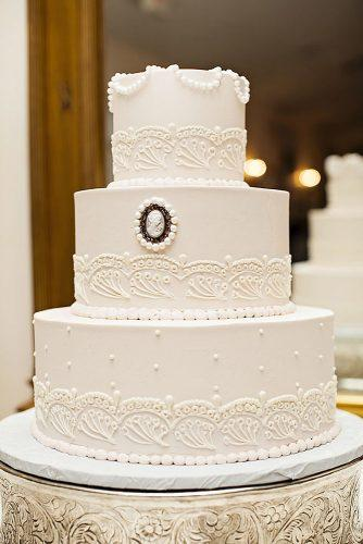 elegant wedding cakes white three tiered cake with vintage decoration with beads and patterns jacquie rives photography