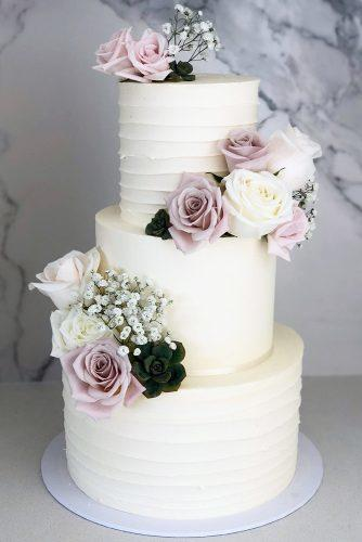 buttercream wedding cakes classic tall white with lilac roses and baby breath blondebakingmama via instagram