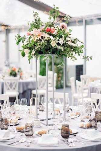 wedding table decorations on a table with a white tablecloth high stand with a bouquet of flowers brancoprata via instagram