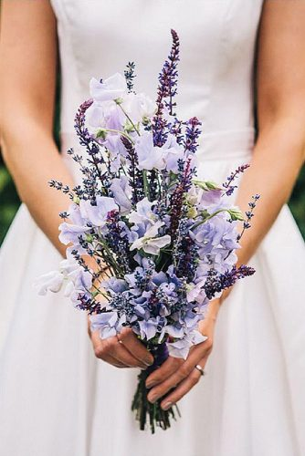 wildflower wedding bouquets the bride is holding a bouquet with delicate flowers and lavender cassandra lane photography