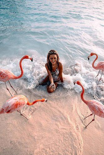 affordable honeymoon packages aruba girl girl feeding pink flamingos at the beach