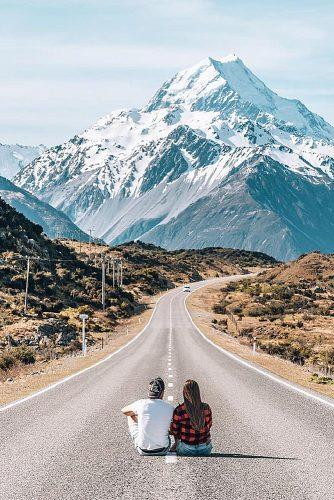affordable honeymoon packages new zealand couple sitting at the road mountains