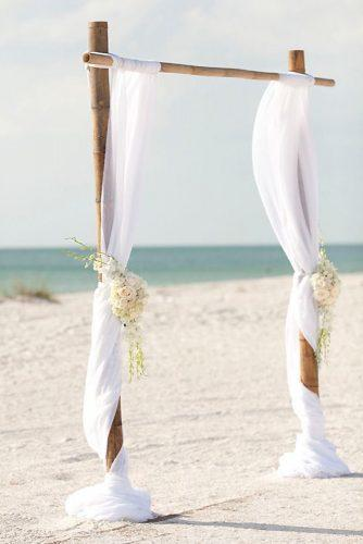 cheap wedding decorations bamboo arch draping a white cloth decorated with white roses stephanie a smith photography