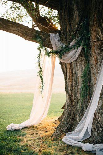 cheap wedding decorations wedding arch of white fabric and greenery fixed on a tree bethany small photography