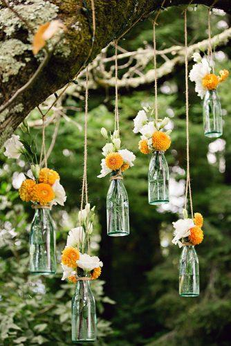 cheap wedding decorations yellow dahlias and white garden roses in glass bottles are suspended on a tree white daisy photography