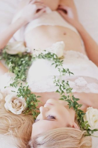 wedding boudoir book bride lying among the flowers love her photography