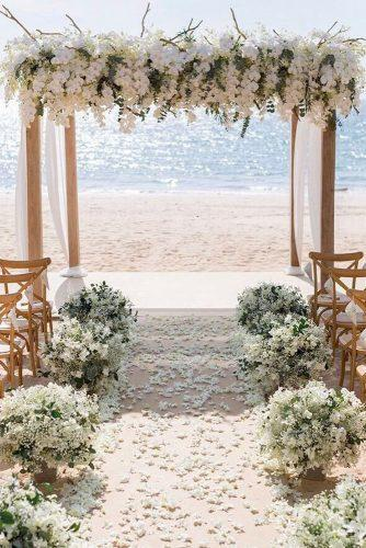 wedding ceremony decorations with white orchids and cloth on the beach iamflower via instagram