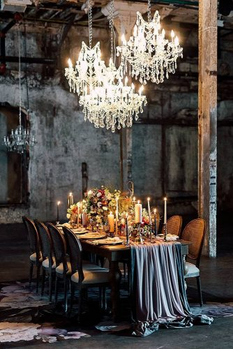 wedding reception decorations a wedding table in an industrial room decorated with a dark tablecloth and many flowers with candles and elegant chandeliers toronto wedding photography via instag