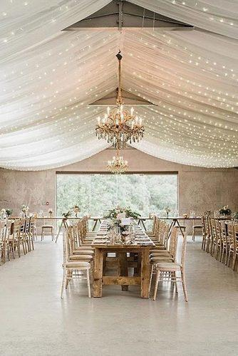 wedding reception decorations in a barn the ceiling is decorated with a white cloth with lights and chic golden chandeliers and long tables charlotte elise events via instagram