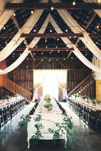 wedding reception decorations in a barn with light bulbs under the ceiling with long tables decorated with flowers and greens a savvy event via instagram