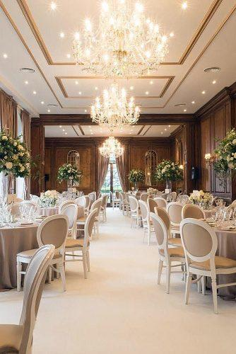 wedding reception decorations in elegant style with large beautiful chandeliers and high vases with flowers on the tables hedsor house via instagram